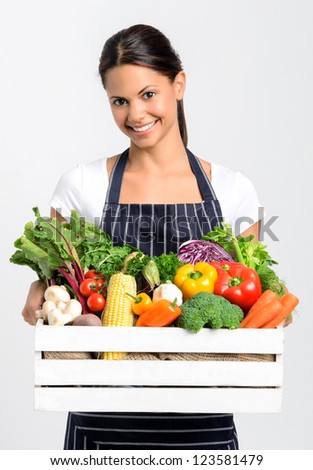 Portrait of happy indian woman chef holding a crate full of fresh organic vegetables on grey background, promoting eating seasonally and sourcing from local producers - stock photo