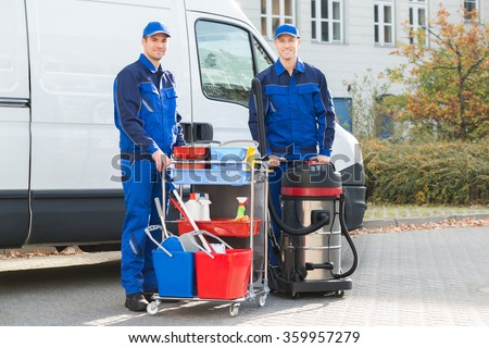 Portrait of happy janitors with cleaning equipment standing against truck - stock photo