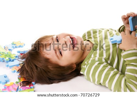 Portrait of happy joyful beautiful little boy playing with puzzle isolated on white background - stock photo