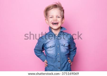 Portrait of happy joyful beautiful little boy. Studio portrait over pink background. - stock photo