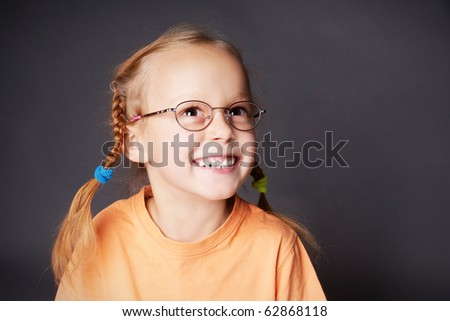Portrait of happy joyful girl in glasses looking up, studio shot - stock photo