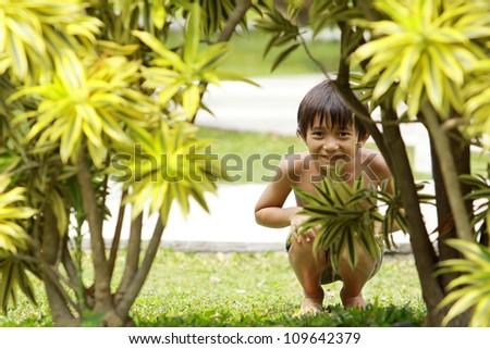 Portrait of happy joyful little boy playing hide and seek in the summer day - stock photo
