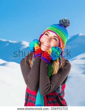 Portrait of happy joyful woman having fun outdoors in the snowy mountains, wearing cute colorful hat, scarf and gloves, with pleasure spending winter holidays - stock photo