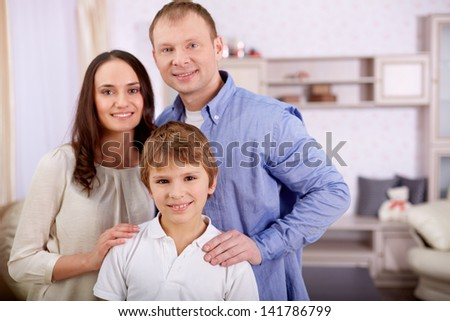 Portrait of happy lad and his parents looking at camera at home