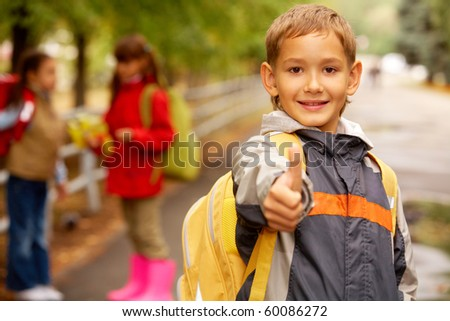 Portrait of happy lad keeping thumb up while looking at camera outside - stock photo