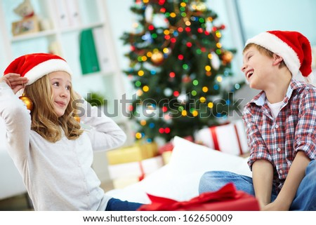 Portrait of happy lad looking at his sister trying on decorative toy balls on Christmas evening - stock photo