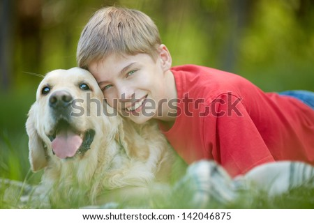 Portrait of happy lad with his friendly pet looking at camera - stock photo