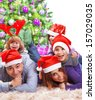 Portrait of happy large family celebrating Christmas holidays at home, lying down near Xmas tree, wearing red Santa hat, New Year eve - stock photo