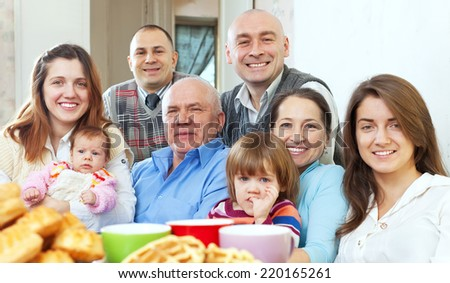 Portrait of  happy large three generations family drinks tea with baked at home