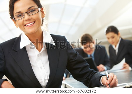 Portrait of happy leader with busy companions working with papers at background - stock photo