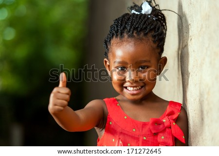 Portrait of happy little african girl doing thumbs up sign outdoors.  - stock photo