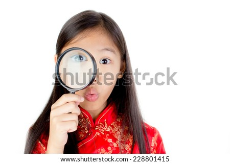 Portrait of happy little Asian child with magnifying glass