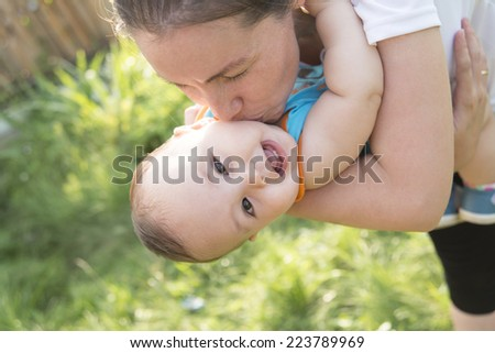 Portrait of happy little asian mom kissing and shake son outdoors on green summer garden with fresh green grass background Cute latin hispanic mother embracing baby boy looking at camera - stock photo