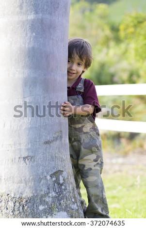 Portrait of Happy Little Boy Hugging a Tree - stock photo