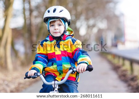 Portrait of happy little boy on bicycle, outdoors. Active leisure with children in winter, sping or autumn. - stock photo
