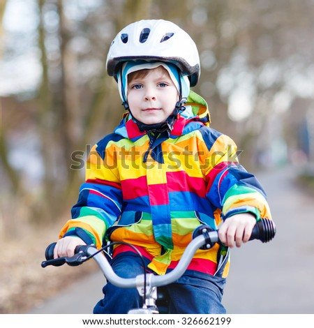 Portrait of happy little boy on bicycle, outdoors. Active leisure with children in winter, sping or autumn.