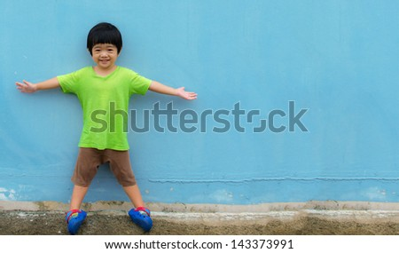 Portrait of happy little boy over blue wall background - stock photo