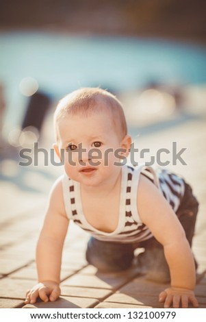 Portrait of happy little boy playing outdoors at dock near the sea - stock photo