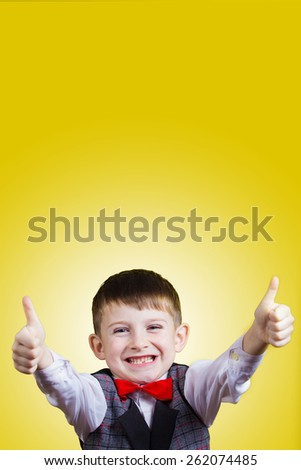 Portrait of happy little boy showing thumbs up gesture wearing costume and a red bow, isolated over yellow background.Funny,happiness. - stock photo