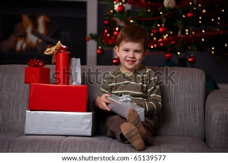 Portrait of happy little boy sitting on couch with christmas presents, smiling.?