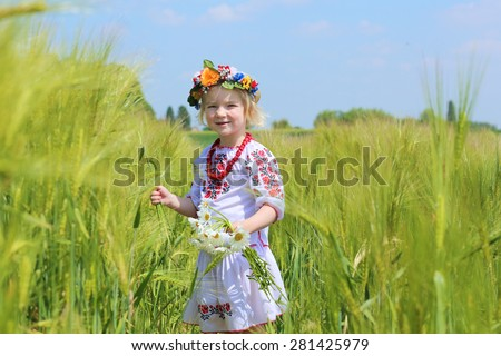 Portrait of happy little child, cute preschooler girl wearing traditional ukrainian dress and holding daisy flowers enjoying nature playing in wheat or barley field on a sunny summer day - stock photo