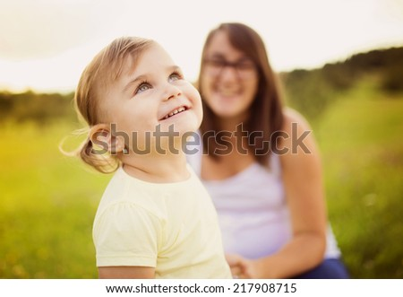 Portrait of happy little daughter holding her pregnant mother�´s hand in the park