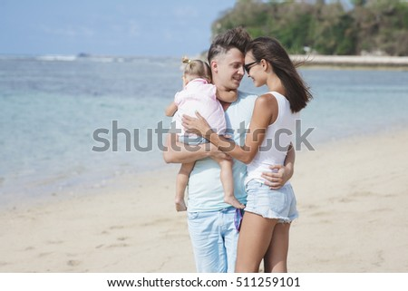 portrait of happy little family on summer vacation at the beach