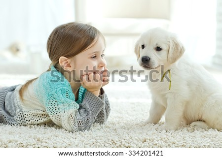 Portrait of happy little girl at home with labrador puppy - stock photo