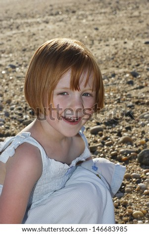 Portrait of happy little girl crouching at beach - stock photo