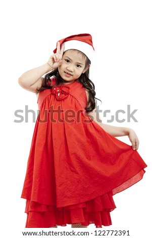 Portrait of happy little girl in Santa dress playing