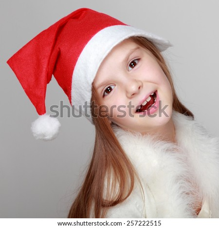 Portrait of happy little girl in Santa hat - stock photo