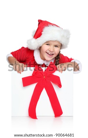 Portrait of happy little girl in Santa hat looks out of Christmas gift box, on a white background