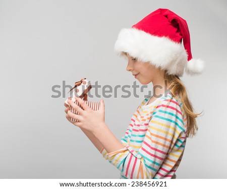 Portrait of happy little girl in santa hat with gift box over white background - stock photo