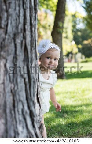 Portrait of happy little girl looking at camera while hiding behind tree trunk