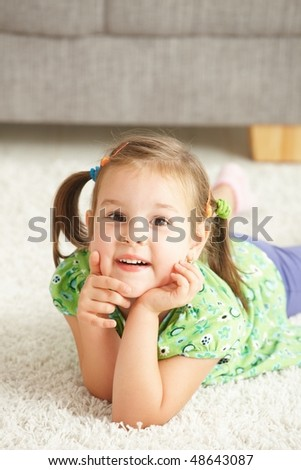 Portrait of happy little girl lying on floor at home looking at camera, smiling. - stock photo