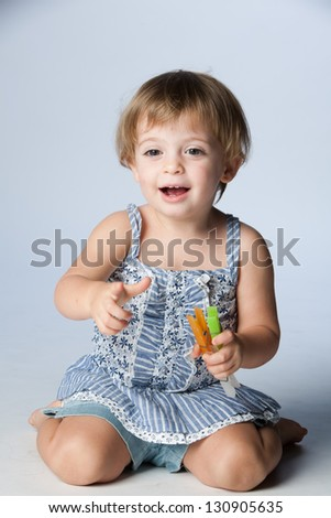 Portrait of happy little girl on her knees. - stock photo