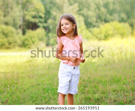 Portrait of happy little girl outdoors in sunny summer day - stock photo