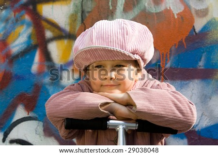 Portrait of happy little girl who is taking a respite near graffiti painted wall - stock photo