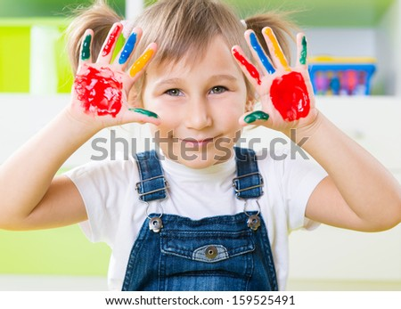 Portrait of happy little girl with colorful pains on hands - stock photo