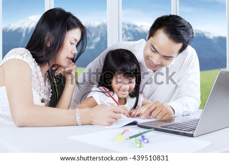 Portrait of happy little girl writing on the book while doing schoolwork with her parents at home - stock photo