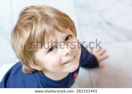 Portrait of happy little kid boy in indoors. Funny child with blond hairs and blue eyes. - stock photo