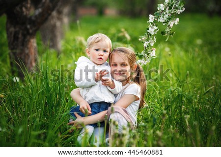 Portrait of happy little sister on the grass - stock photo