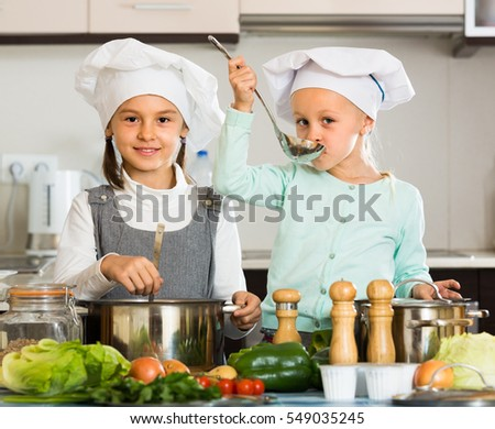 Portrait of happy little sisters in caps learning how to cook