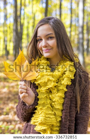 Portrait of happy lovely teenage girl  in the forest, autumn season, holding a fallen leaf