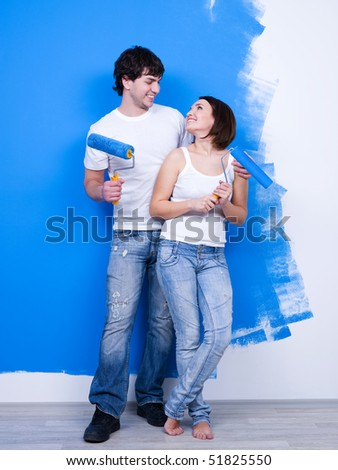 Portrait of happy loving cheerful couple near the painted wall