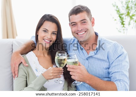 Portrait of happy loving couple toasting wine glasses at home
