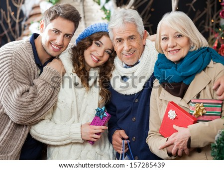 Portrait of happy loving family with Christmas presents and shopping bags standing in store - stock photo
