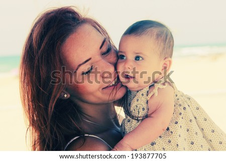 Portrait of happy loving mother and her baby at the beach - stock photo