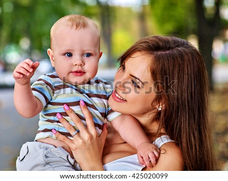 Portrait of happy loving mother holding on hand her baby outdoors in park. Baby look at camera. - stock photo