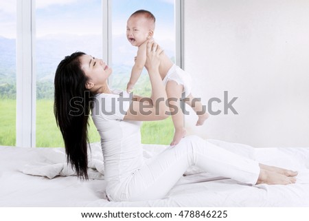 Portrait of happy loving mother throws up her baby in the bedroom